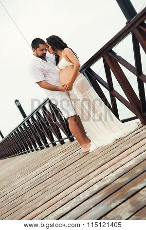 Happy Pregnant Couple In White Clothes On The Sea Coast On Wooden Bridge