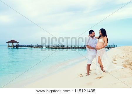Beautiful Young Pregnant Couple On The Caribbean Coast. Happy Pregnancy