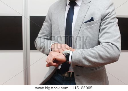 Handsome man in elegant gray suit watching at his wristwatch