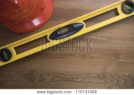 Yellow Building Level And Red Helmet On The Wood Table