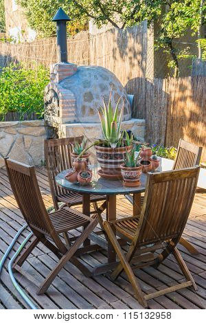 Table And Chairs In The Wooden Terrace Of The Garden