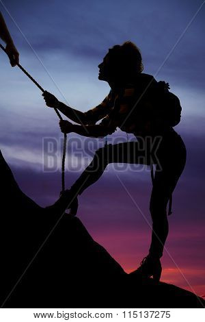 Silhouette Of A Woman Climbing Steep Hill And Rope