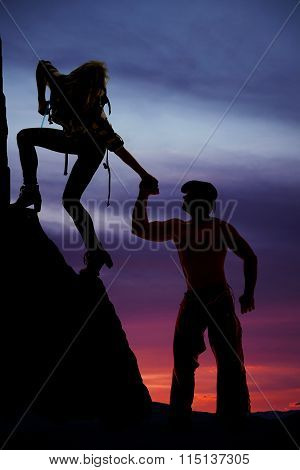 Silhouette Of A Woman Climbing Reaching Down For Man