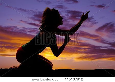 Silhouette Of A Woman On Her Knees Hands Up Pleading
