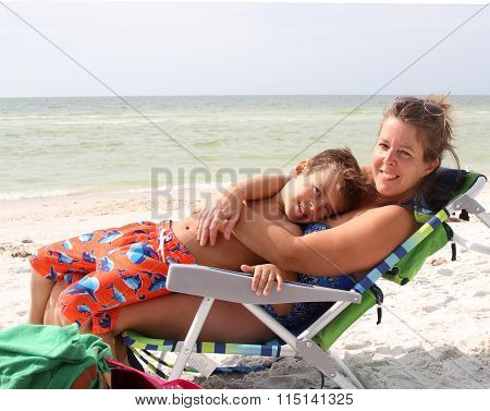 Mother lying and hugging child on a sun chair on a  sandy beach in Florida