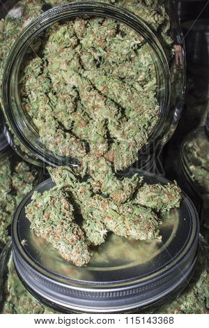Glass Jar Full of Marijuana Buds Spilling Out