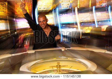 Young Man Playing Roulette In Casino Betting And Winning Money