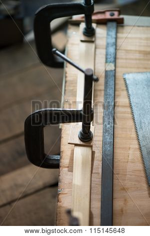 Woodworking. Wood working project on work bench in a dim workshop. Clamped pieces of wood with c-clamps and bar clamp. Shot in low key and shallow depth of field. Focus is on forehand clamp pad.