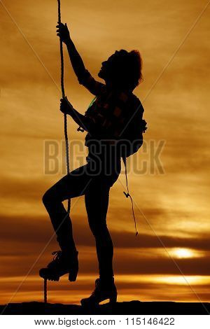 Silhouette Of A Woman Ready To Climb A Rope