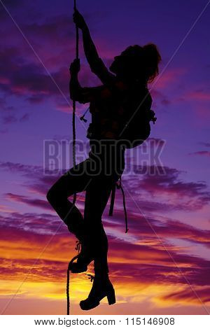 Woman Climbing Up A Rope With A Pack On