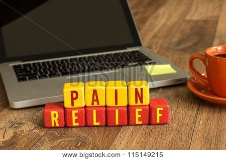 Pain Relief written on a wooden cube in a office desk