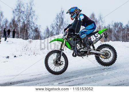 closeup man biker rides a motorcycle on a snowy hill