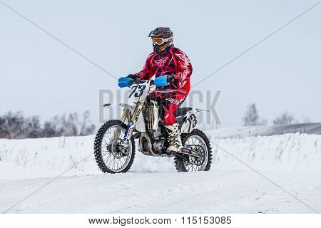 racer on a motorcycle rides through snowy road race motocross