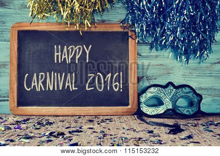 an elegant blue and black mask and a chalkboard with the text happy carnival 2016 on a rustic wooden surface full of confetti