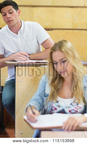 Cheating student copying notes at the lecture hall