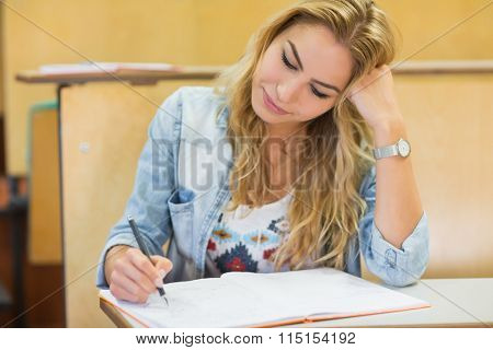 Thoughtful attractive student writing during class in lecture hall