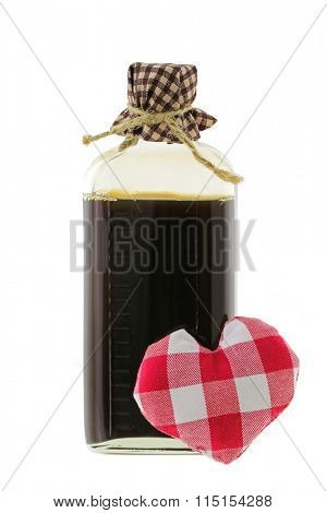 A glass bottle of love potion in brown with a red gingham heart in the front, isolated on white