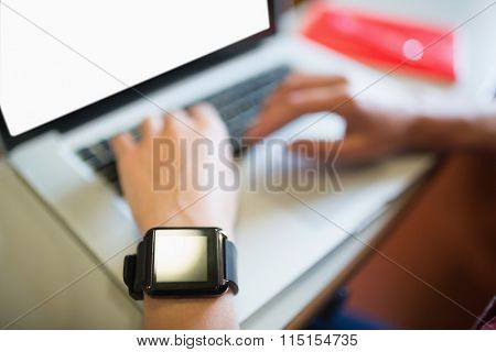 Cropped image of female student using laptop in lecture hall