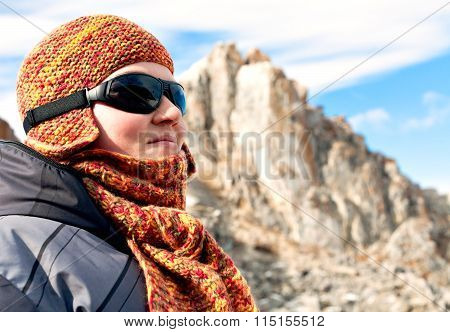 Portrait of a girl in orange scarves and hats against the blue sky and snowy mountains. Sport mountain sunglasses. Bright sunny winter day. Wrapped in a scarf. Olkhon Island on Lake Baikal.