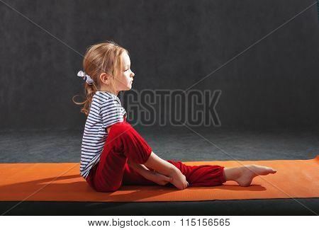 Little girl doing exercises on the mat for yoga.