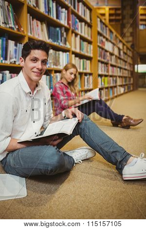 Smiling male student revising on floor in library
