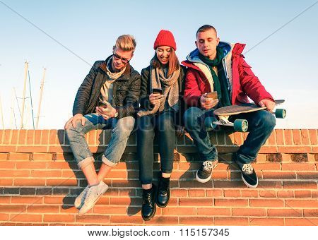 Group Of Friends Using Smartphone Sitting On Low Briks Wall - Young People Addicted To Mobile