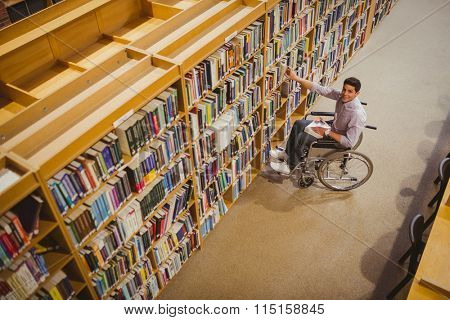 Student in wheelchair picking a book from shelf in library