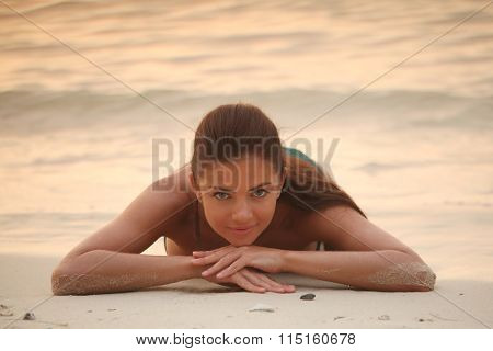 Beautiful woman lays on sand of beach in sunset