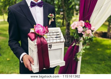Groom Hold Wedding Box With Flower And Lilac Ribbon On Wedding Ceremony