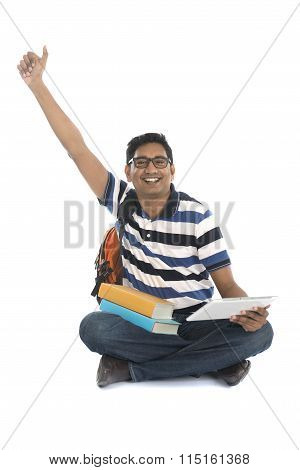 Smiling Indian Male Surfing While Sitting On The Floor