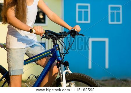 The hands of young woman sitting on bicycle