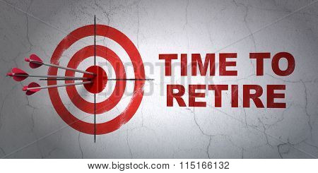 Time concept: target and Time To Retire on wall background