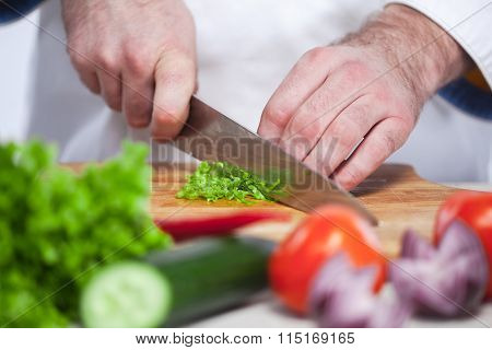 Chef cutting a green lettuce his kitchen