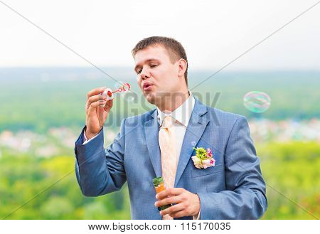 groom blowing bubbles