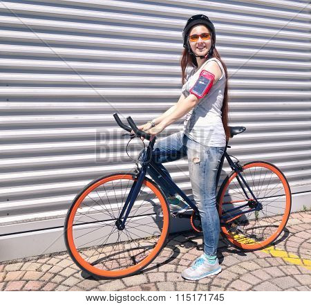 Young Happy Woman With Sport Bike And Mobile Armband Standing Next To Wall - Female Cyclist
