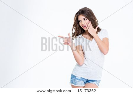 Portrait of a young happy woman pointing finger away isolated on a white background