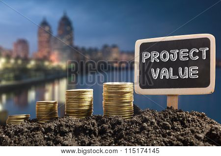 Project value- Financial opportunity concept. Golden coins in soil  Chalkboard on blurred urban back