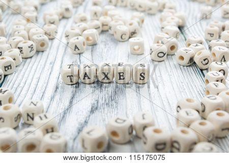 Taxes word written on wood block. Wooden ABC.