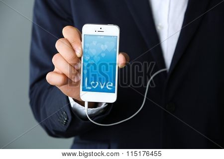 Music smartphone with romantic screensaver in businessman hand, close-up