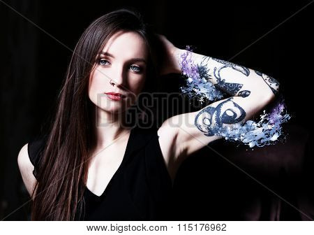 Young beautiful girl with tattoo and abstract color background