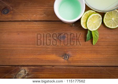 close up of body lotion, cream and limes on wood