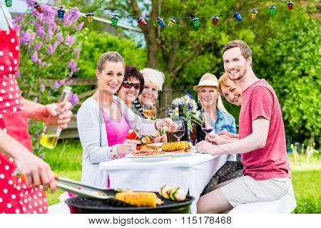 Man grilling meat and vegetables on garden party, his friends eating the bbq meat