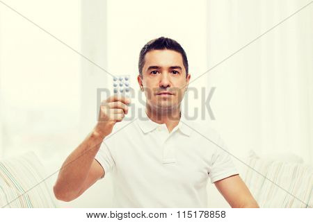 man showing pack of pills at home