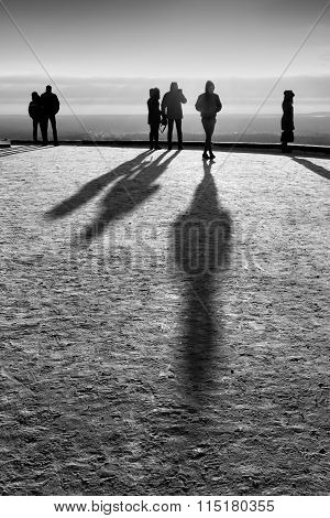 People Standing Looking In Winter With Their Shadows