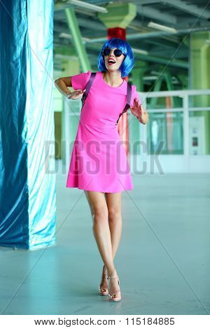 Young woman in mini dress posing like doll inside empty building
