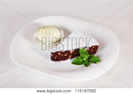 chocolate brownie cake with powdered sugar and mint plate isolated white background