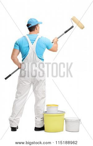 Rear view studio shot of a male decorator painting with a paint roller isolated on white background