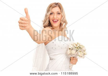 Joyful young bride holding a wedding bouquet and giving a thumb up isolated on white background