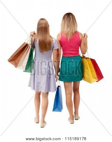 back view of  two walking women  with shopping bags. backside view of person.  Rear view people collection. Isolated over white background.  Young girls in colorful dresses with shopping go away.