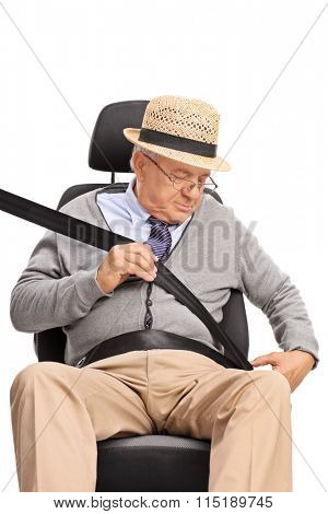 Vertical shot of a senior gentleman fastening a seatbelt seated on a car seat isolated on white background